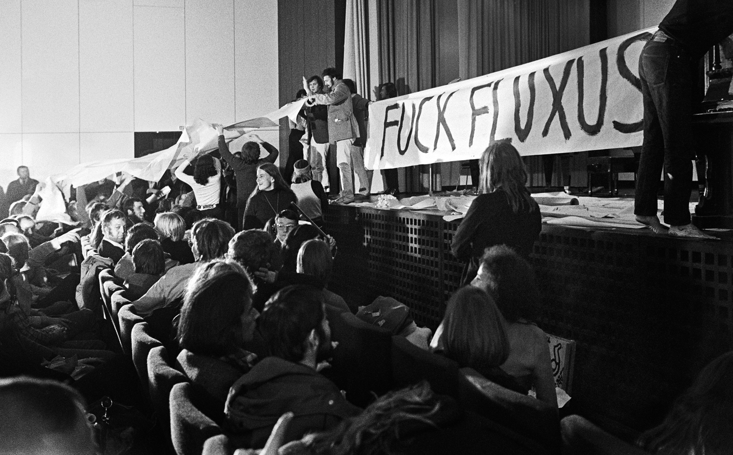 Fluxus concert on the occasion of the exhibition Happening & Fluxus, on the left next to the banderole Harald Szeemann, Cologne Kunstverein, 1970. Photo: Ad Petersen